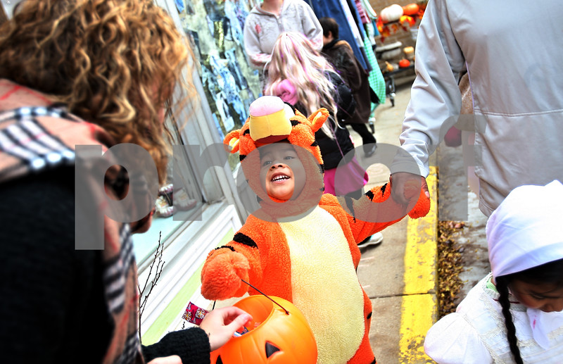 Beck Diefenbach  -  bdiefenbach@daily-chronicle.com<br /> <br /> Angelo Gonzalez, 4, trick or treats as Tiger and recieves candy from Danielle Holland, left, at Crackerjax in DeKalb, Ill., on Saturday Oct. 31, 2009.