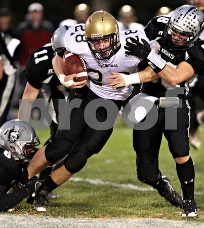 Beck Diefenbach  -  bdiefenbach@daily-chronicle.com<br /> <br /> Sycamore running back Joe Dougherty (28, left) pushes through Kaneland defensive back Ryley Bailey (88) during the first quarter of the class 5A playoff game at Kaneland High School in Maple Park, Ill., on Saturday Oct. 31, 2009.