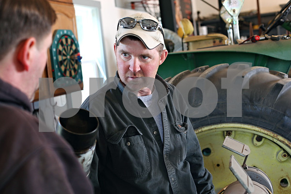 Beck Diefenbach  -  bdiefenbach@daily-chronicle.com<br /> <br /> Ben Anderson, of Waterman, discusses engine parts with a friend while overhauling the engine on his tractor in the garage on his homestead in Waterman, Ill. Anderson is against the installation of wind turbines which may surround parts of his property.
