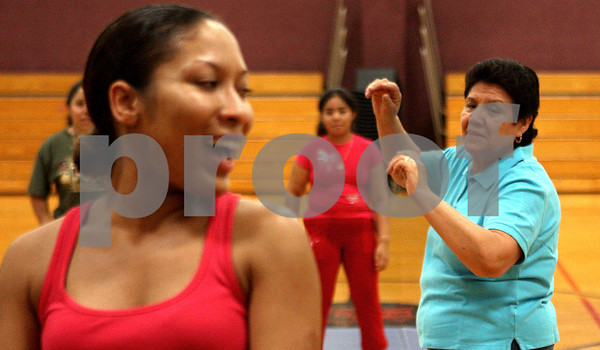 Rob Winner – rwinner@daily-chronicle.com<br /> The Latino Action Group in DeKalb has joined with the Dekalb Park District to offer an excercise program specifically for minorities. During Tuesday's program at Haish Gym in DeKalb, Maria Garcia (right) follows the dance moves of Emmali Richmond (left), as Richmond instructs the class.<br /> 06/30/2009