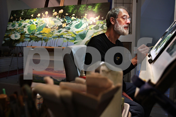 Beck Diefenbach  -  bdiefenbach@daily-chronicle.com<br /> <br /> Professional artist James Winn works on his realist painting of lotus lilies from the Mississippi River in the studio of his Sycamore home on Wednesday October 21, 2009. Winn now paints smaller versions of his painting (top left) which are more likely to sell in this tough economy.