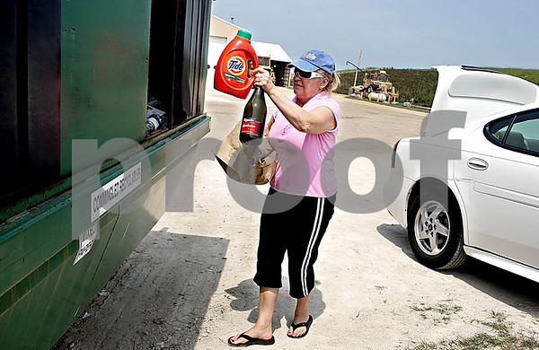 "Rob Winner – rwinner@daily-chronicle.com<br /> On Tuesday afternoon, Merrie Schyvincht of Sycamore empties her vehicle filled with recyclables at the DeKalb County Recycling and Disposal Facility. ""I have been doing this long before they coined the term green,"" said Schyvincht who has been recycling for more than 25 years. <br /> 08/04/2009"