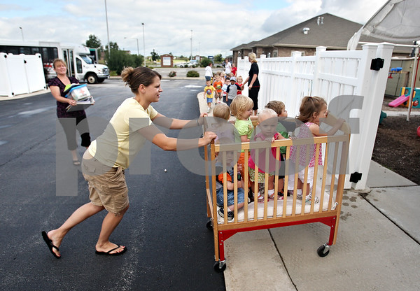 Beck Diefenbach  -  bdiefenbach@daily-chronicle.com<br /> <br /> Teacher Kathy Potvin, left, wheels her toddlers back into their classroom following a monthly fire drill at Land of Learning Child Care Center in Sycamore, Ill., on Thursday Aug. 20, 2009.