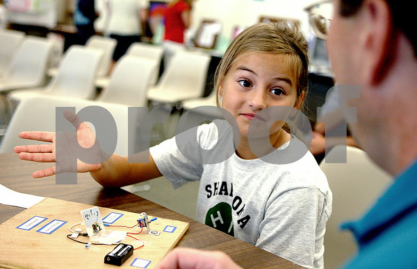 Rob Winner – rwinner@daily-chronicle.com<br /> Katie Schilling, 9, of Shabbona, explains how her electricity project works to 4-H judge John Boesche during the DeKalb County 4-H Show at the DeKalb County Farm Bureau in Sycamore on Thursday morning.<br /> 07/16/2009