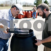 Beck Diefenbach  -  bdiefenbach@daily-chronicle.com<br /> <br /> Left, Scott Pumroy, director of the DeKalb County Soil and Water Conservator District, shows off a compost barrel to Cason Snow, of Sycamore, who was picking up his rain and compost barrels at the DeKalb County Farm Bureau in Sycamore, Ill., on Friday April 17, 2009.