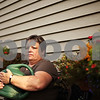 Beck Diefenbach  -  bdiefenbach@daily-chronicle.com<br /> <br /> Michelle Friedlund poses outside her Sycamore home on Tuesday August 25, 2009. Friedlund, who suffers from a Chiari malformation in her brain, says the gardening in her backyard can be therapeutic.