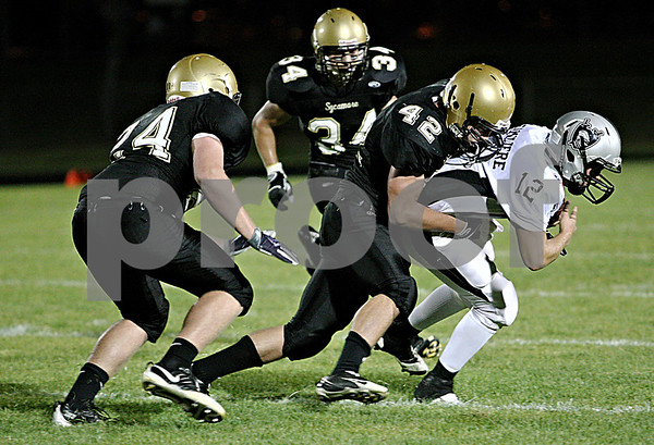 Rob Winner –  rwinner@daily-chronicle.com<br /> Sycamore's Harlan Johnson (42) sacks Kaneland quarterback Joe Camiliere for a loss of three yards late in the first half of Friday night's game in Sycamore.<br /> 09/18/2009