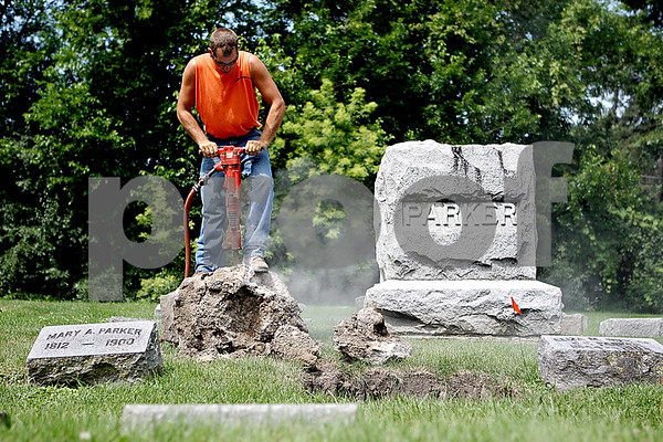 Rob Winner – rwinner@daily-chronicle.com<br /> On Friday at Elmwood Cemetery in Sycamore, Lenny Reynolds of Image Monuments and Cemetery Services removes old foundation from a headstone. Later in the day, new foundation was poured and the headstone was reset into the ground.<br /> 07/23/2009