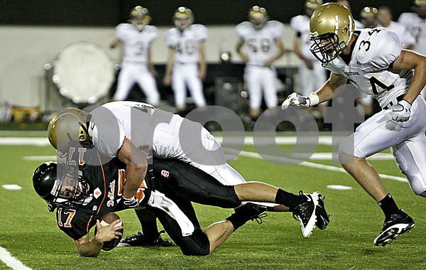 Rob Winner rwinner@daily-chronicle.com<br /> DeKalb quarterback Frank Petras (17) is sacked by Sycamore's Harlan Johnson in the first half for a loss of eight yards.<br /> 09/11/2009