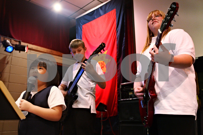 """Beck Diefenbach  -  bdiefenbach@daily-chronicle.com<br /> <br /> From left, singer Grace Cho, 6, Ethan Hansen, 12, and Allie Halberson, 12, play during band practice for """"The Reborn"""" at the Salvation Army in DeKalb, Ill., on Wednesday Sept. 23, 2009."""