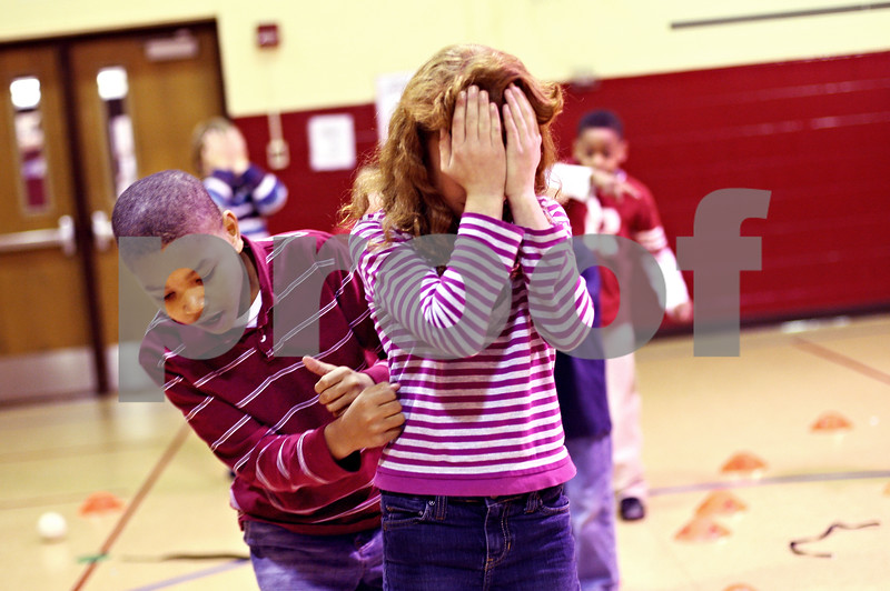 Beck Diefenbach  -  bdiefenbach@daily-chronicle.com<br /> <br /> Fifth grader Janeceia Holler, right, covers her eyes as second grader Javaughn Owens, left, guides her through an obstacle course during an after school program run in conjunction with the YMCA at Little John Elementary School on Tuesday Dec. 15, 2009.