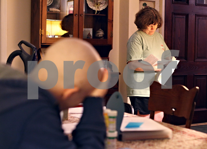 Beck Diefenbach  -  bdiefenbach@daily-chronicle.com<br /> <br /> Kevin's mother, Diane, looks over their current insurance covered medical bills totaling $123,000 at their DeKalb home on Friday April 17, 2009. Kevin stills has a lot of treatments ahead of him, including a bone marrow transplant.