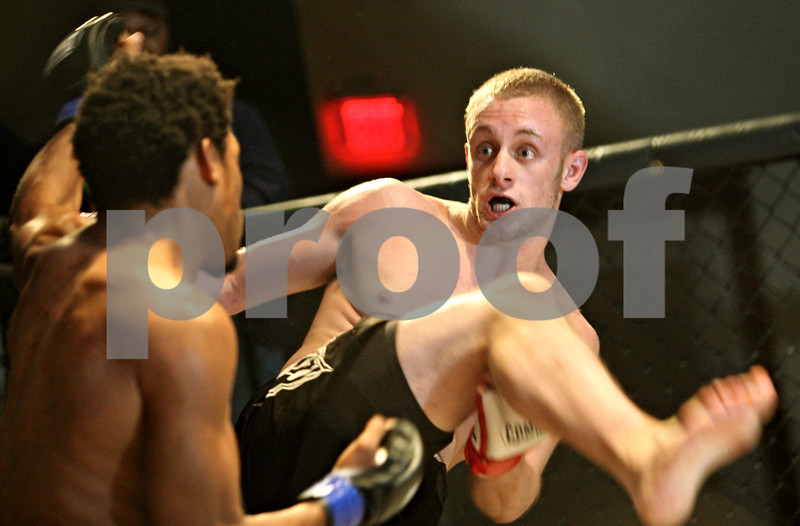 Beck Diefenbach  -  bdiefenbach@daily-chronicle.com<br /> <br /> Steven Kick, 18, of Sandwich, Ill., swings to kick his opponet Mark Mack during Power Fights 14, an amateur cage-fighting mixed-martial arts event at the Timber Creek Inn and Suites, in Sandwich, on Saturday Oct. 21, 2009.