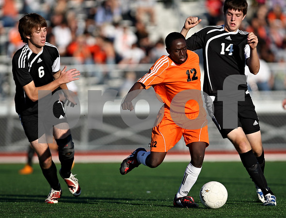 Beck Diefenbach    bdiefenbach@daily-chronicle.com<br /> DeKalb's Thomas Ogundige (12, center) slips between Sycamore's Andy Wallace (6, left) and Shane Toms (14) during the first half of the game at the Northern Illinois University Soccer and Track and Field Complex in DeKalb, Ill., on Monday Sept. 5, 2009.