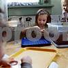 Beck Diefenbach – bdiefenbach@daily-chronicle.com<br /> <br /> Right, Nora Vietmier, 4, watches as Paige Walk, 5, examines a worm in her hand from the compost bin at Home Away from Home day care in DeKalb, Ill., on Thursday March 12, 2009. The class will use dirt from the compost bin in their garden in the spring.