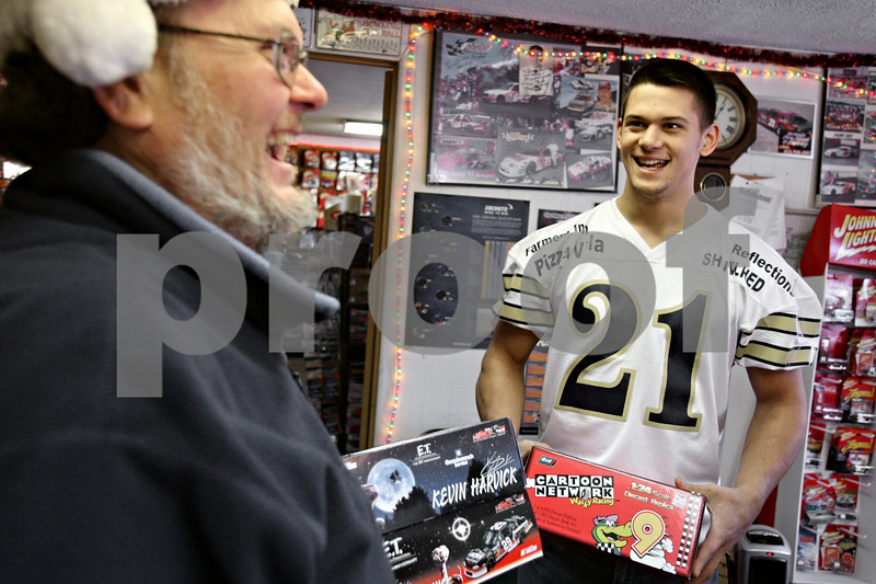 Rob Winner – rwinner@daily-chronicle.com<br /> Brian Prentice (left), owner of Brian's Pro Shop & Hobby located in DeKalb, Ill., donates die cast car models to Jace Quimby, of Kirkland, on Saturday December 19, 2009. Quimby will raffle the items donated by Prentice to raise funds to take part in a football program which takes place in Hawaii in 2010.