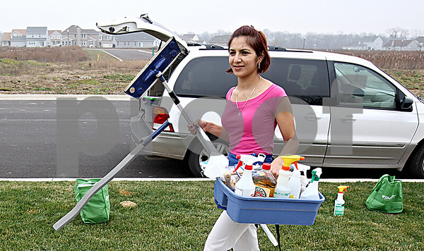 Rob Winner – rwinner@daily-chronicle.com<br /> Miriam Serna, of A Clean Healthy House, carries cleaning supplies into a clients home in Genoa on Monday afternoon.<br /> 11/23/2009