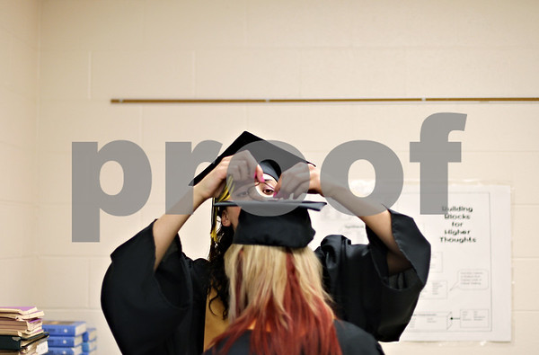 Beck Diefenbach  -  bdiefenbach@daily-chronicle.com<br /> <br /> Graduating senior Sam Thrower attaches the tassel to her classmate Elle Smith before the ceremony at Sycamore High School in Sycamore, Ill., on Sunday May 31, 2009.
