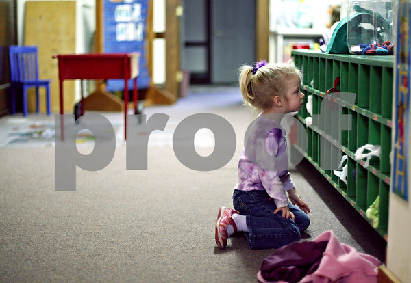 Beck Diefenbach  -  bdiefenbach@daily-chronicle.com<br /> <br /> Lauren Jordal, 3, sits on the floor as she looks for her painting shirt in her cubbie hole during preschool at United Church of Christ in Shabbona, Ill., on March 24, 2009. The church is hosting a fundraiser to replace the carpeted floor in the preschool with tile.