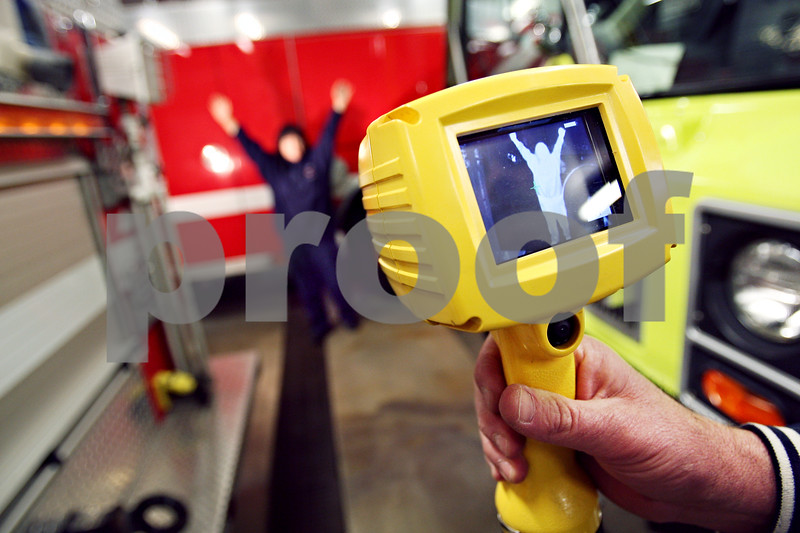 Beck Diefenbach  -  bdiefenbach@daily-chronicle.com<br /> <br /> Emergency medical technician Mel Needleham poses for the thermal imaging camera at the Maple Park Fire Department. The camera, purchased with help from the DeKalb County Community Foundation, can help locate hidden fires, hot stops and people in a burning building.