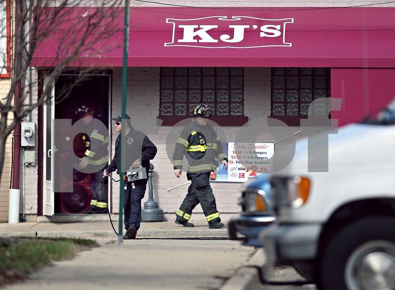 Beck Diefenbach  -  bdiefenbach@daily-chronicle.com<br /> <br /> DeKalb firefighters exit the back door to KJ's Tap and Grill in DeKalb, Ill., on Friday March 27, 2009.