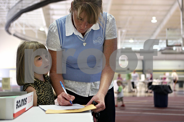 Rob Winner – rwinner@daily-chronicle.com<br /> On Tuesday afternoon at Sycamore High School, Jamisan Matalonis, 6, talks with her mother Anne while registering Jamisan for first grade at North Grove School.<br /> 08/11/2009