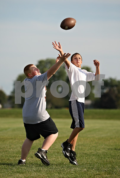 Beck Diefenbach  -  bdiefenbach@daily-chronicle.com<br /> <br /> St. Mary's Anthony Szala, right, and Huntley's Nate Keller reach for the ball during receiving drills at a junior high football camp hosted by DeKalb High School in DeKalb, Ill., on Wednesday July 29, 2009.