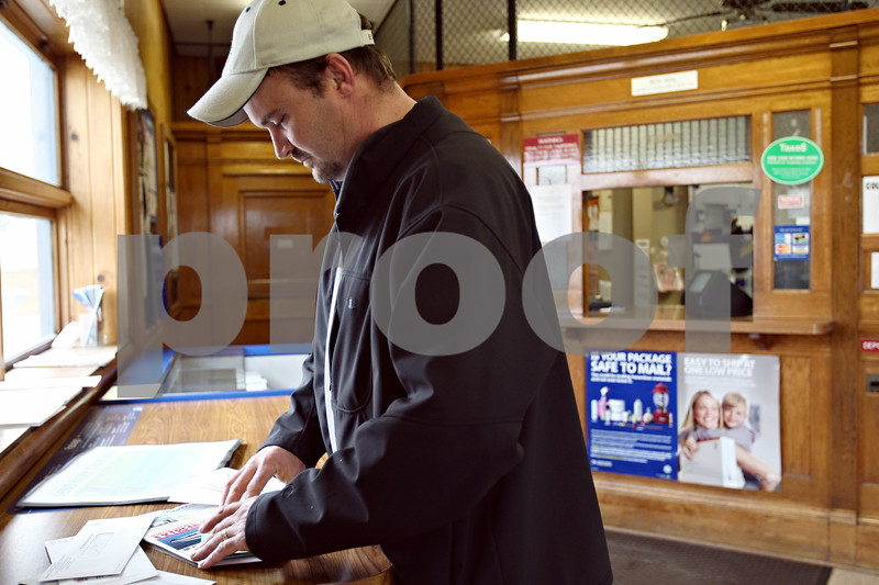 """Beck Diefenbach – bdiefenbach@daily-chronicle.com<br /> <br /> John Gilberth, of Waterman, goes through his mail after picking it up from the Waterman Post Office in Waterman, Ill., on Tuesday March 10, 2009. Delivery service may be cut from six days to five in hopes of reduced spending.  """"It's fine with me,"""" said Gilberth concerning the possible canceling of one day of delivery service."""