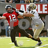 Rob Winner – rwinner@daily-chronicle.com<br /> NIU quarterback Chandler Harnish throws the ball away while being pursued by Idaho's Aaron Lavarias in the third quarter. Harnish was flagged for intentional grounding and the Huskies were pinned deep in their territory.<br /> 09/26/2009
