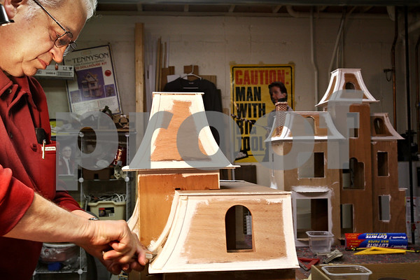 Beck Diefenbach  -  bdiefenbach@daily-chronicle.com<br /> <br /> Lee Newtson applies shingles to the rook of one of his two doll houses he is constructing in the basement of his Cortland, Ill., home on Monday Dec. 14, 2009. One of the doll houses will be delivered to the White House in Washington D.C. and the second will be sold to raise funds to benefit Fisher House which serves families of veterans at Hinds Veterans Affairs Hospital in Maywood, Ill.