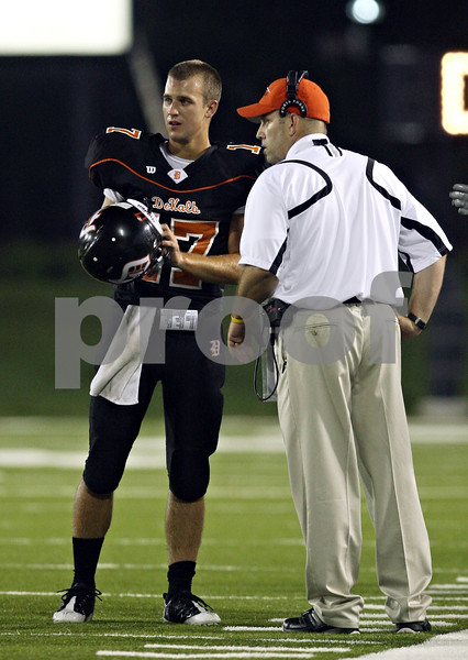 Beck Diefenbach  -  bdiefenbach@daily-chronicle.com<br /> <br /> DeKalb quarterback Frank Petras (17) talks with head coach Marty Sanders during the first quarter of the game against Ottawa Township High School at Huskie Stadium of Northern Illinois University in DeKalb, Ill., on Friday Aug. 28, 2009.