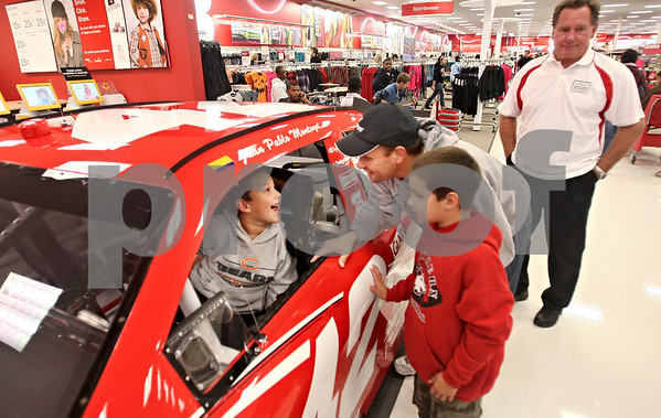 Beck Diefenbach  -  bdiefenbach@daily-chronicle.com<br /> <br /> (In the car) Braydon Borgardt, 6, enjoys the view from the Target Nascar race car normally driven by driver Juan Pablo Montoya as his father Brian, of DeKalb, and brother Blake, 8, look on during the opening of the rebuilt Target Store in DeKalb, Ill., on Tuesday Oct. 6, 2009.
