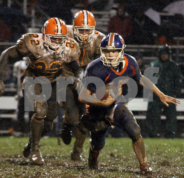 Wendy Kemp/For The Daily Chronicle<br /> Genoa-Kingston quarterback Craig Billington gets chased by two Byron defenders during Friday's playoff game.<br /> Genoa 10/23/09