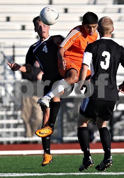 Beck Diefenbach    bdiefenbach@daily-chronicle.com<br /> DeKalb's Anthony Vivero (1, right) leaps for the ball with Sycamore's Trevor Cervenka (4) during the first half of the game at the Northern Illinois University Soccer and Track and Field Complex in DeKalb, Ill., on Monday Sept. 5, 2009.