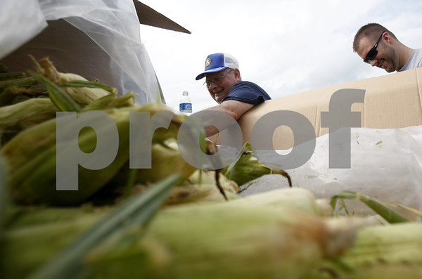 EMILY OLSON | emolson@daily-chronicle.com<br /> Dave Wood, 71, and Adam Massier, 24 of the DeKalb of the Kiwanis Club of DeKalb prepare ears of corn to be roasted at Corn Fest at the DeKalb Taylor Municipal Airport on Friday. The group expects to roast more than 4,000 ears of corn over the 3-day festival.