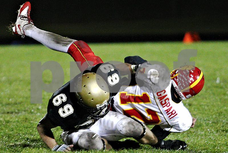 Rob Winner – rwinner@daily-chronicle.com<br /> <br /> Sycamore's Dorian Hryniewicki sacks Batavia quarterback Noel Gaspari during the first half of Friday night's game.<br /> <br /> 10/09/2009
