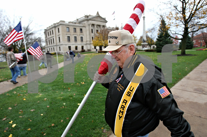 Rob Winner – rwinner@daily-chronicle.com<br /> Vietnam veteran Lonnie Stojan carries a flag to be placed along the sidewalk in front of the DeKalb County Courthouse in Sycamore on Friday October 30, 2009. Earlier this year, a tumor was found in his left lung, a presumptive after-effect caused by Agent Orange.