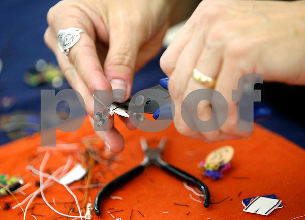 ROB WINNER   rwinner@daily-chronicle.com<br /> Nickie Olivier, of South Elgin, prepares a pin for one of her customers at her table at the St. Mary's Craft Show on Friday afternoon.