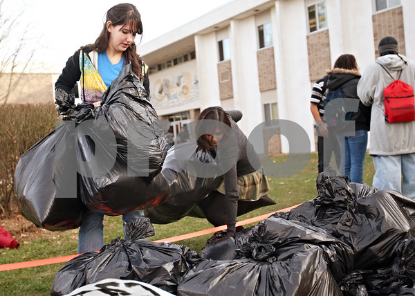 Beck Diefenbach  -  bdiefenbach@daily-chronicle.com<br /> <br /> DeKalb High School senior Chloe Helser, left, and junior Siti Asma collect bags of plastic recyclables which sat on display in front of the school in DeKalb, Ill., on Thursday Nov. 12, 2009. Helser is president of the Ecobuds Club, a student environmental group, which organized the collection of recyclables and presentation so that students and community members would notice the importance of using a recycling bin instead of a trash can.