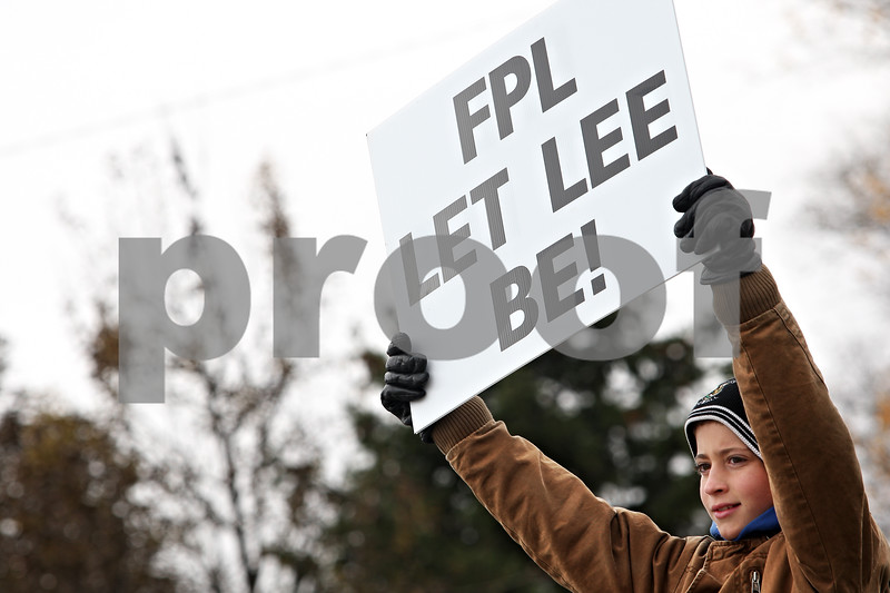 """Beck Diefenbach  -  bdiefenbach@daily-chronicle.com<br /> <br /> Caleb Flex, 12, of Waterman, holds a sign asking for the wind farm developer Florida Power and Light to """"let Lee be"""" during an anti-wind farm protest on the corner of County Line Road and Lee Road in Lee, Ill., on Saturday Oct. 24, 2009."""