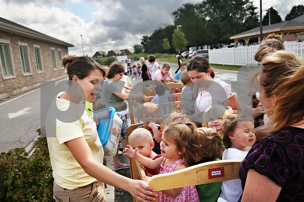 Beck Diefenbach  -  bdiefenbach@daily-chronicle.com<br /> <br /> Teacher Kathy Potvin, left, consoles her toddlers during a monthly fire drill at Land of Learning Child Care Center in Sycamore, Ill., on Thursday Aug. 20, 2009.