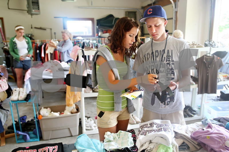 Beck Diefenbach  -  bdiefenbach@daily-chronicle.com<br /> <br /> Kelsey Hayes, 17, and her boyfriend Vinnie Laudicini attach price stickers to clothing for the Hayes family garage sale at their DeKalb home on Thursday June 18, 2009. Hayes and her two sisters will use the profits from their old clothes to pay for new school clothes.