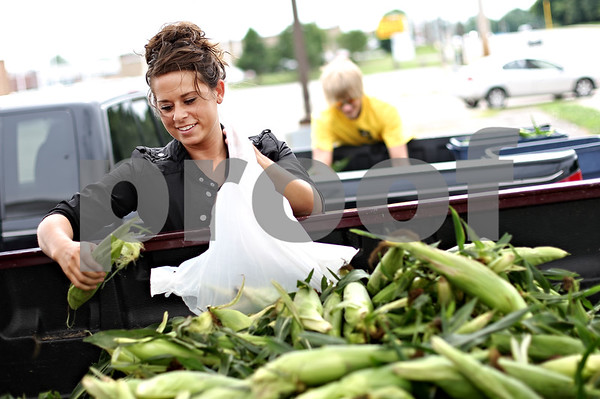 Beck Diefenbach  -  bdiefenbach@daily-chronicle.com<br /> <br /> Megan Klock, of Kirkland, bags sweet corn from her family's farm for customers at the corner of Sycamore Road and Greenwood Acres Drive in DeKalb, Ill., on Friday July 24, 2009. This is the first weekend of the season the Klock family is selling sweet corn in DeKalb.