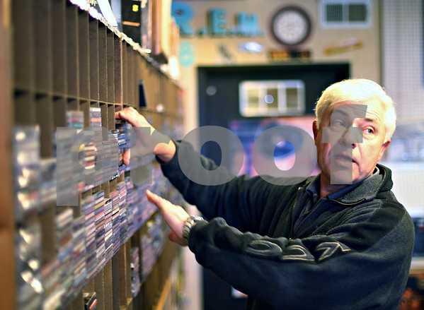 Beck Diefenbach  -  bdiefenbach@daily-chronicle.com<br /> <br /> Store owner Mike Korcek sifts through CD racks at Record Rev in DeKalb, Ill., on Tuesday April 21, 2009. After 35 years, Korcek is retiring and Record Rev is closing it's doors.