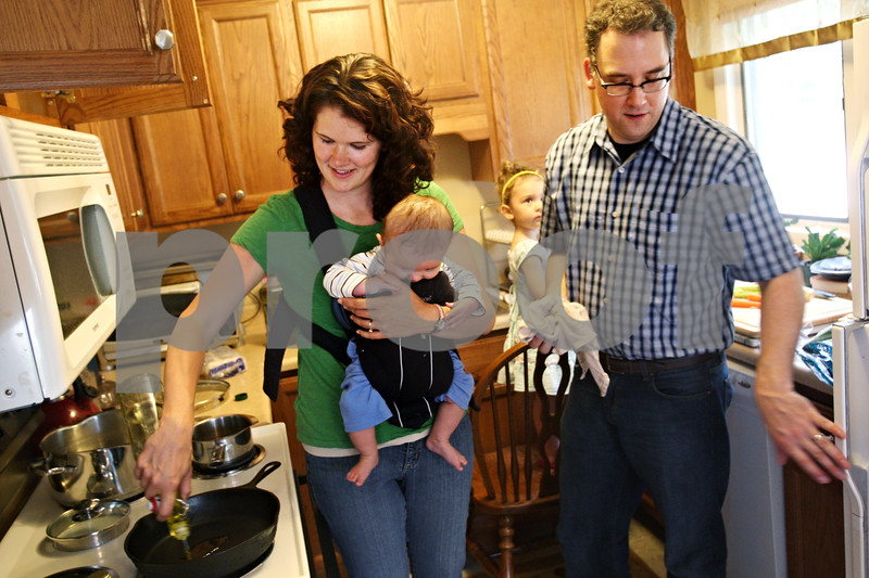 Beck Diefenbach  -  bdiefenbach@daily-chronicle.com<br /> <br /> Zach Sands, right, and wife Jamie, with son Alexander, 4 months, prepare dinner at their Sycamore home on Thursday July 2, 2009. Zach is moving his family to Moldova on a Fulbright scholarship after recently graduating with a master's degree in english from Northern Illinois University.