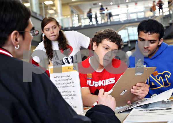 Beck Diefenbach  -  bdiefenbach@daily-chronicle.com<br /> <br /> Northern Illinois University students and Huskies United volunteers Justin Kuryliw (center) and Kenil Thakkar (right) look over the contact information of NIU staff member Margaret Myles (far left) as she registers for the National Marrow Donor Program in Barsema Hall on the NIU campus in DeKalb, Ill., on Thursday April 30, 2009.