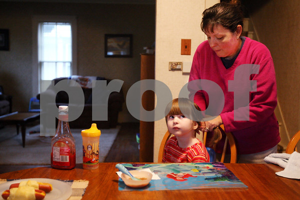 Beck Diefenbach  -  bdiefenbach@daily-chronicle.com<br /> <br /> Rosie Hadley, right, ties back her daughter Morgan's hair before they eat dinner in their new home in DeKalb, Ill., on Friday Oct. 2, 2009.