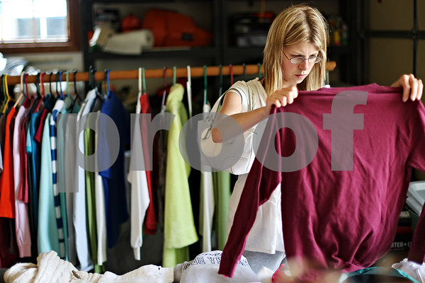 """Beck Diefenbach  -  bdiefenbach@daily-chronicle.com<br /> <br /> Kristin Flesher, of Genoa, searches through clothes at the hayes family garage sale in DeKalb, Ill., on Thursday June 18, 2009. Flesher, who visits garage sales weekly, said """" (I) never know what I'm gonna find when I come."""""""