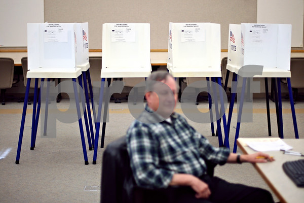 Beck Diefenbach  -  bdiefenbach@daily-chronicle.com<br /> <br /> Empty voting booths sit behind election judge John Linderoth, of Sycamore, during early voting at the Legislative Center in Sycamore, Ill., on Monday March 30, 2009.