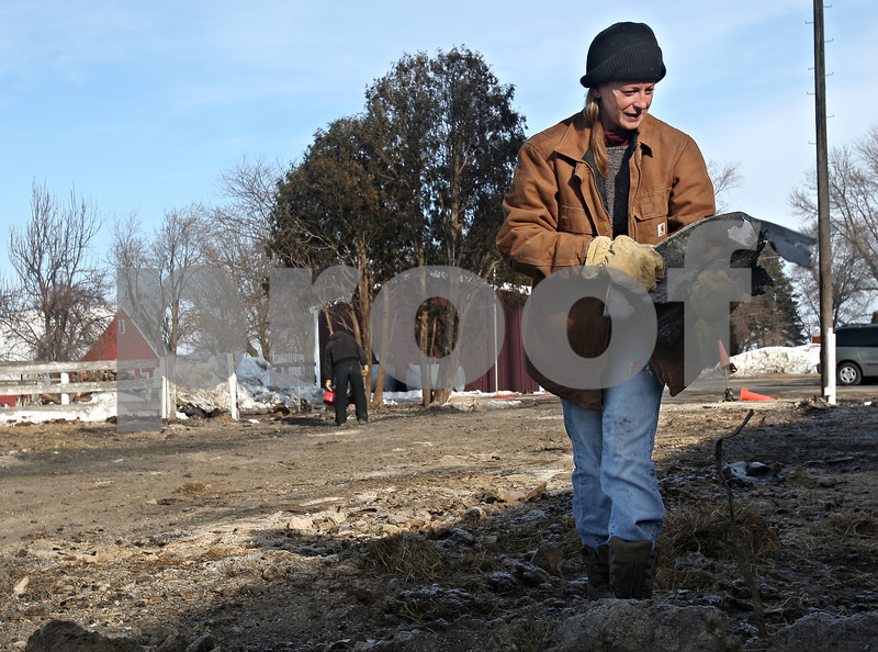 Beck Diefenbach  -  bdiefenbach@daily-chronicle.com<br /> <br /> Amy Klink, owner of JAK Ranch, picks up debris left in the remains of her horse barn which burned down Thursday on her family's ranch in Clare, Ill., on Friday Feb. 6, 2009.